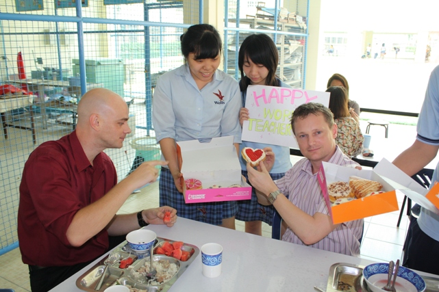 Wells seniors Ji Hae and Pauleen offer donuts to Mr. Brian and Mr. Graham during lunch break.