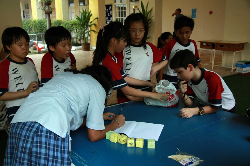 "A secondary student playing a game of ""Rice Dice Calculation,"" organized by Grade 4B students"