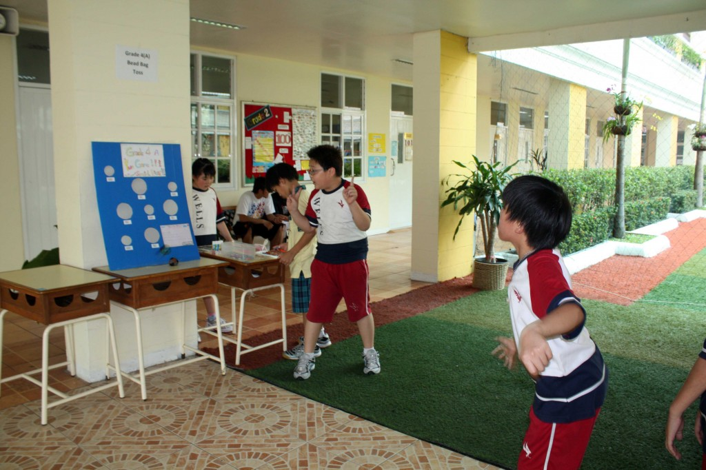 A student aiming to hit the bean bag in the correct spot, an activity organized by Grade 4A students
