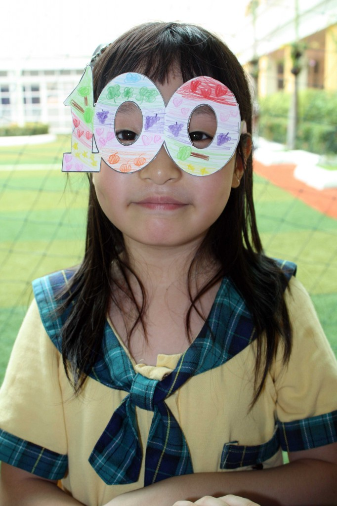 "A grade one student showing her colorful pair of ""100 glasses"""