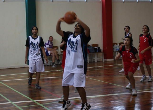 Power forward Ramita Sachasiri (gr 8) lays one with twin sister Richika backing her up.