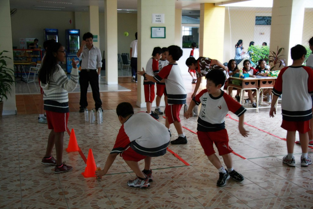 "A group of students playing ""Bottle Bowling,"" organized by Grade 5 students"